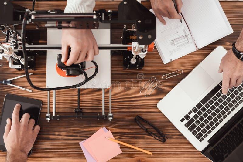 Tre uomini stanno lavorando a creare una stampante 3d teamwork Uno degli uomini funziona con un computer immagini stock