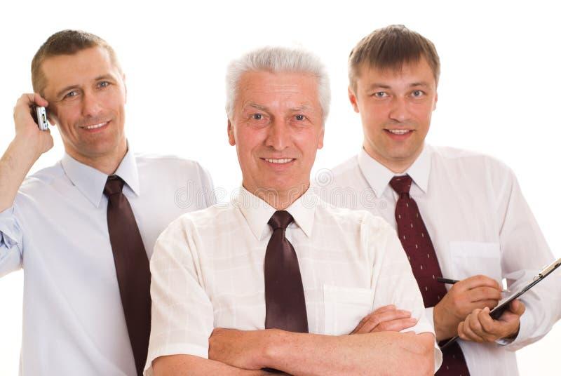 Tre uomini su un bianco fotografia stock