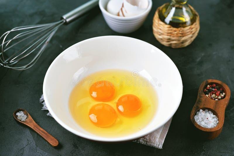 Tre uova crude in una ciotola per la cottura delle uova rimescolate immagine stock libera da diritti