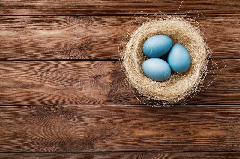 Tre uova di Pasqua blu dipinte dall'ibisco, in un nido con le piume su un fondo di legno Simbolo di Pasqua Copi lo spazio fotografie stock