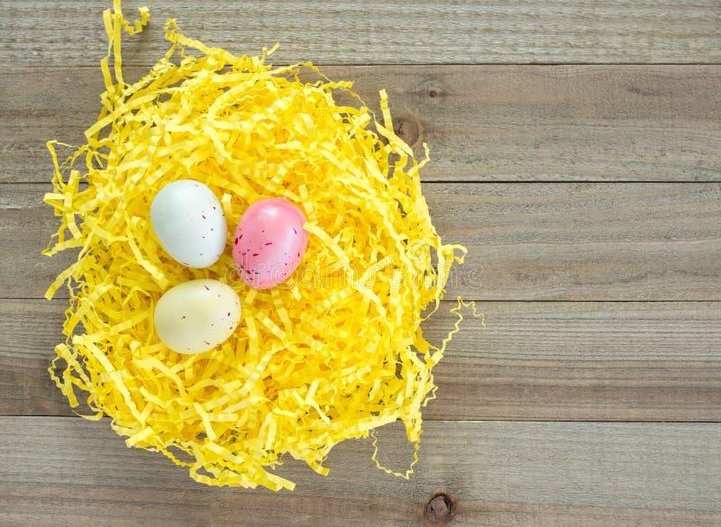 Tre uova di Pasqua macchiate variopinte nell'erba gialla di Pasqua su un fondo di legno immagine stock