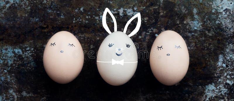 Tre uova di Pasqua sveglie con i fronti, fondo felice del coniglietto di pasqua immagini stock
