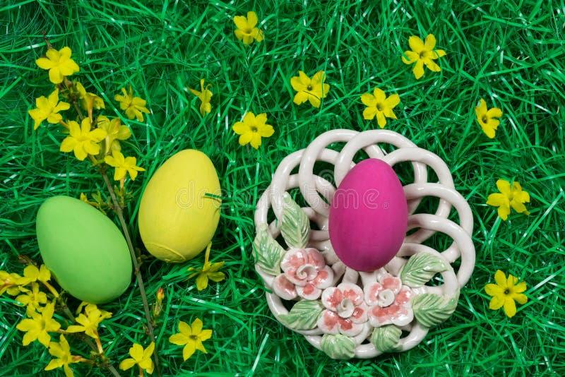 Tre uova di Pasqua variopinte, ciotola decorativa e fiori gialli in erba artificiale verde immagine stock