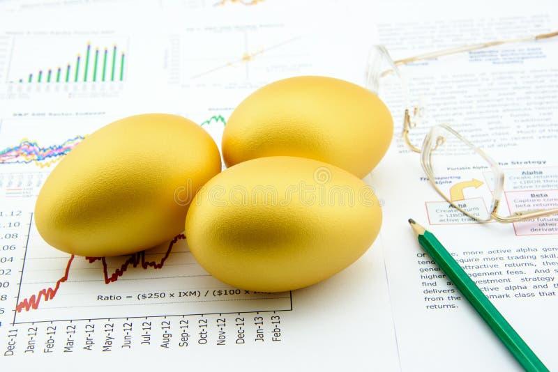 Tre uova dorate con una matita ed i vetri dell'occhio sopra l'affare ed i resoconti sommari finanziari immagini stock libere da diritti