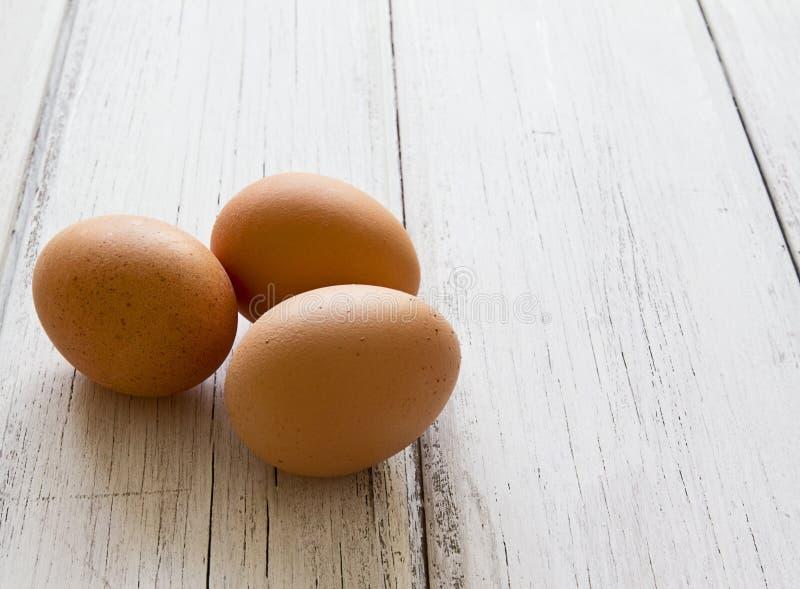 Tre uova fresche su una priorità bassa di legno immagini stock