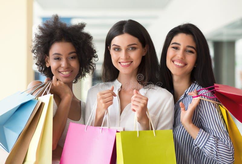 Tre upphetsade kvinnor med färgglade påsar som shoppar i galleria arkivbild