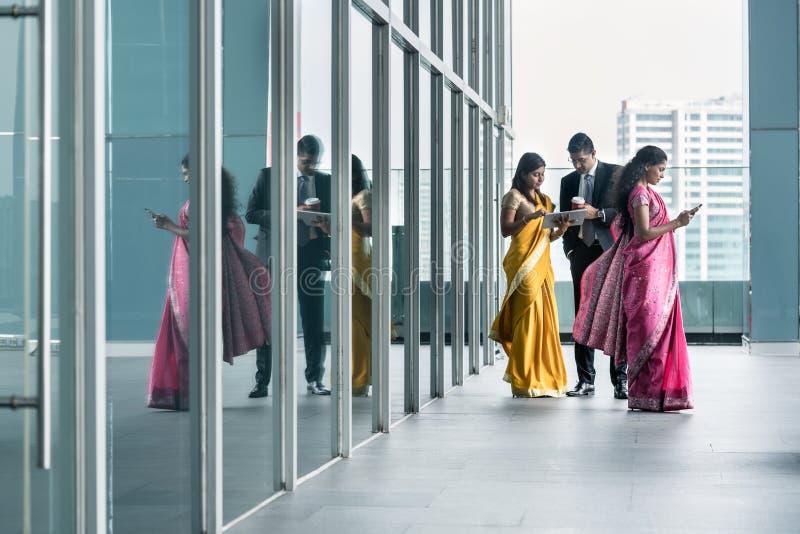 Tre upptagna indiska affärspersoner som använder tekniskt avancerade apparater arkivfoto
