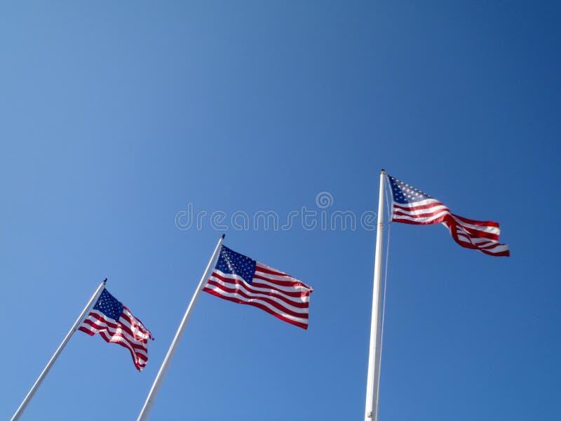 Tre USA flaggor vinkar i luften arkivbilder
