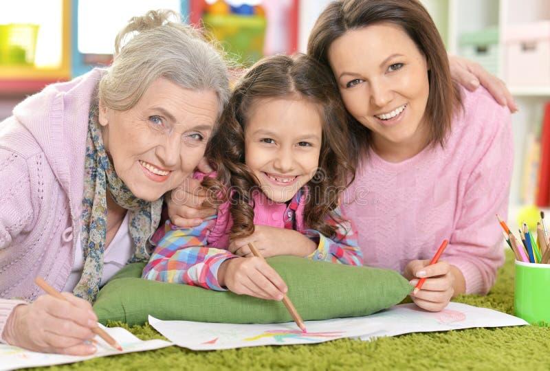 Tre utvecklingar av kvinnor från en familj som ligger på golv och dr arkivbilder