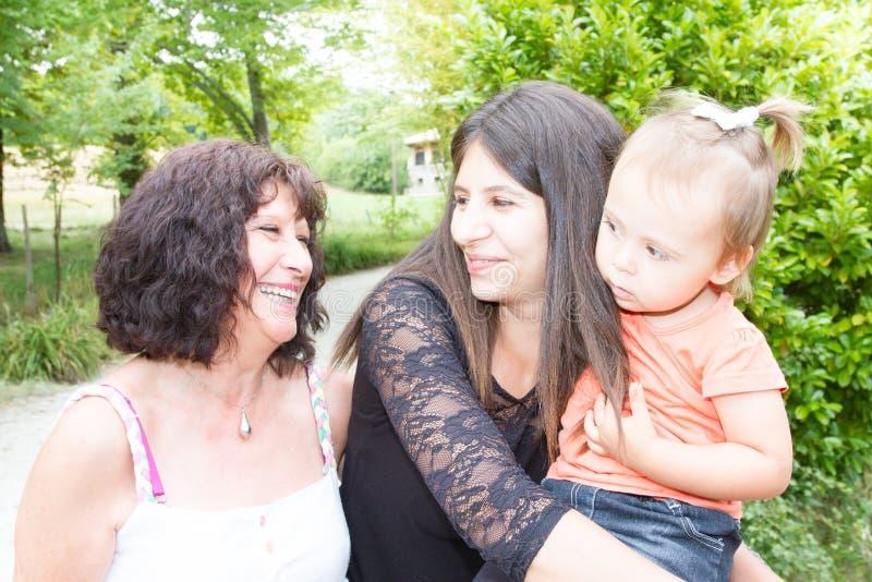 Tre utvecklingar av kvinnor härlig farmor, moder och dotter kramar att le royaltyfri bild