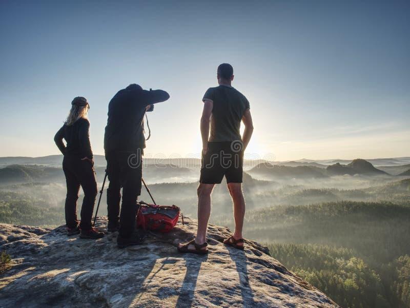 Tre vänfotografer att diskutera och ta fotoet mot solnedgång arkivfoton