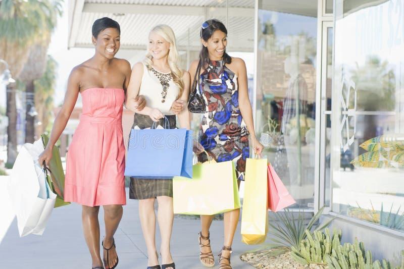 Tre vänner går sidan - förbi - sid i shoppinggalleria royaltyfria foton