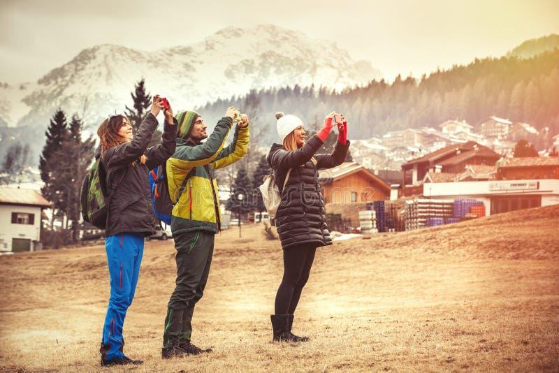 Tre vänner i bergen ta för bild fotvandra royaltyfri foto