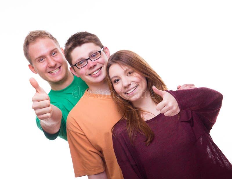 Tre vänner med tumbs up och ler arkivbilder