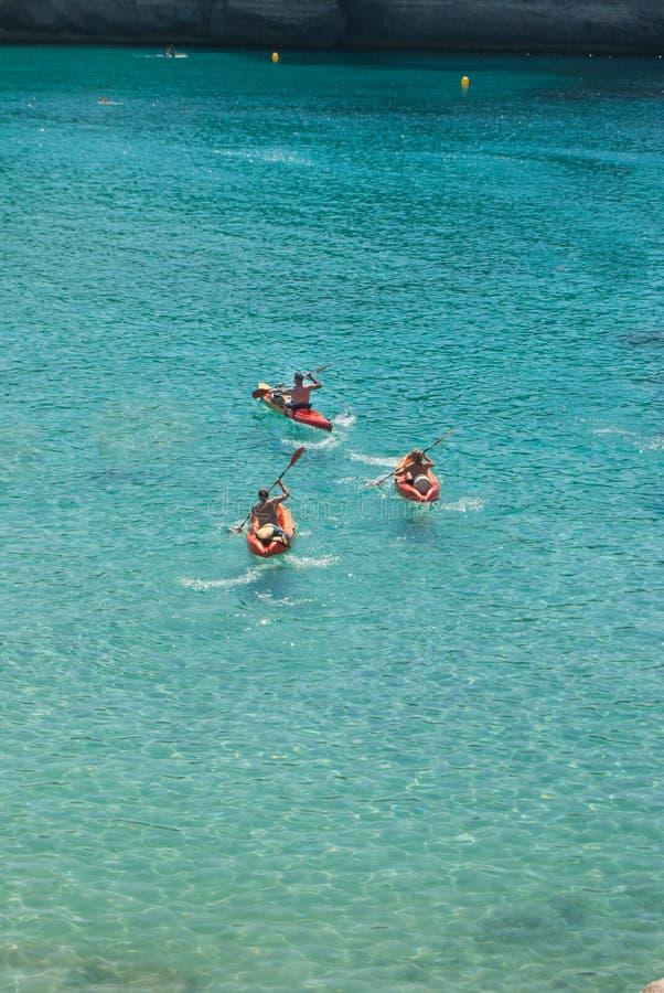 Tre vänner på röda kajaker i havet royaltyfri fotografi