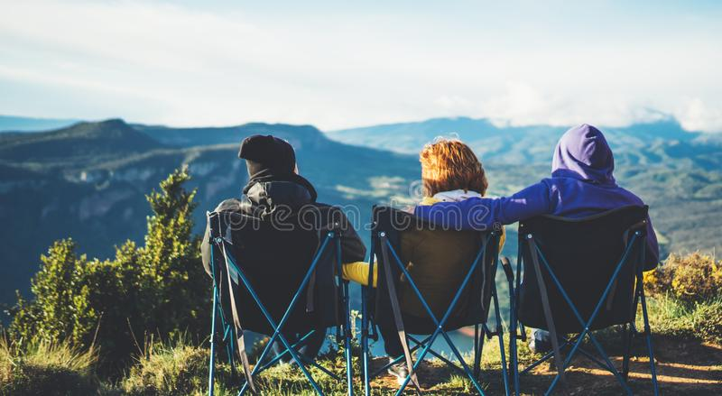 Tre vänner sitter i campa stolar överst av ett berg, tycker om handelsresande naturen, och omfamningen, turister ser in i avstånd arkivbilder