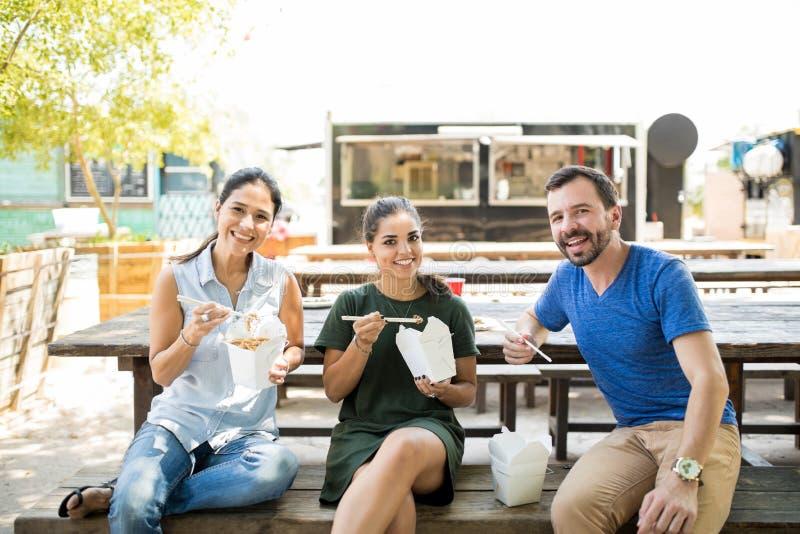 Tre vänner som äter för avhämtning mat fotografering för bildbyråer