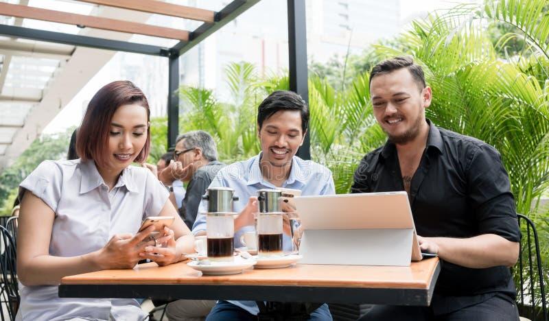 Tre vänner som använder apparater, förband till den trådlösa internet n fotografering för bildbyråer