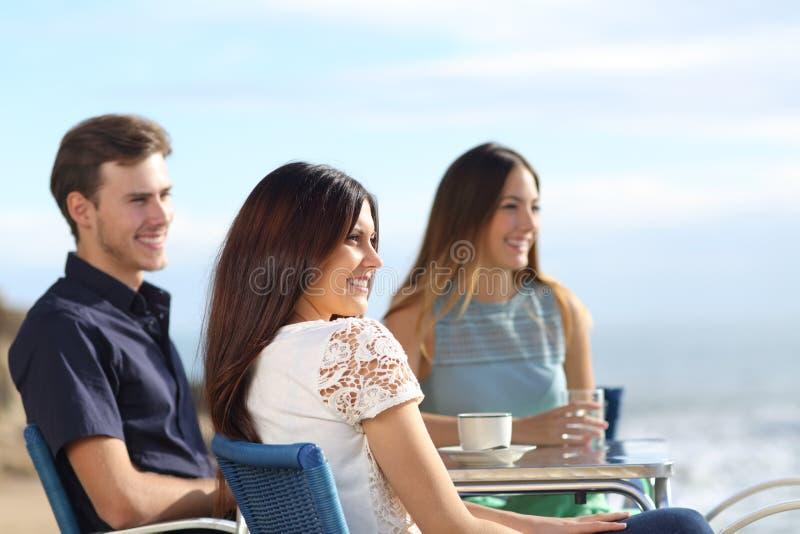 Tre vänner som beskådar havet från en stång royaltyfria bilder