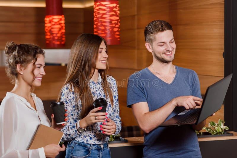 Tre vänner som dricker coffe och ser skärmen av anteckningsboken arkivbilder
