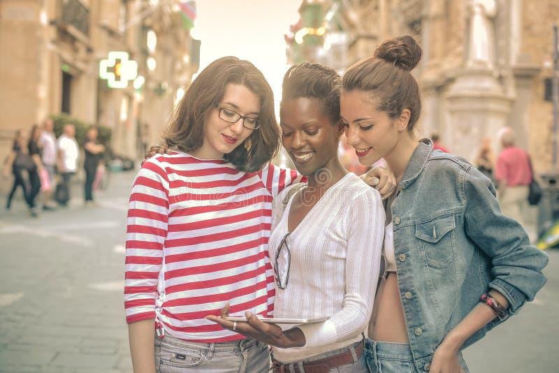 Tre vänner som håller ögonen på skärmen av en minnestavla royaltyfria foton