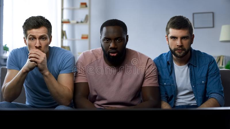 Tre vänner som håller ögonen på spänt fotbollkonkurrens på den stora skärmen, mästerskap royaltyfri fotografi