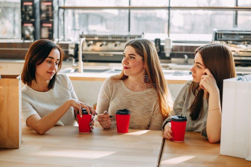 Tre vänner som har en stor tid på kafét unga gruppkvinnor royaltyfria bilder