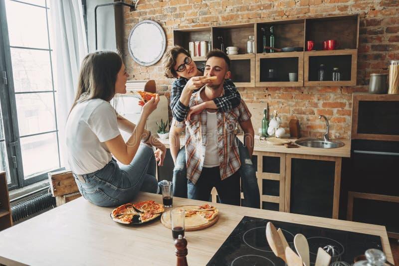 Tre vänner som har gyckel som äter pizza på partiet arkivfoton