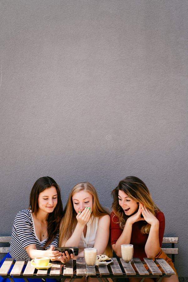 Tre vänner som shoppar direktanslutet genom att använda den smarta telefonen arkivbilder
