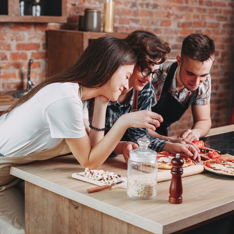 Tre vänner som smakar lagad mat tillsammans pizza arkivfoton