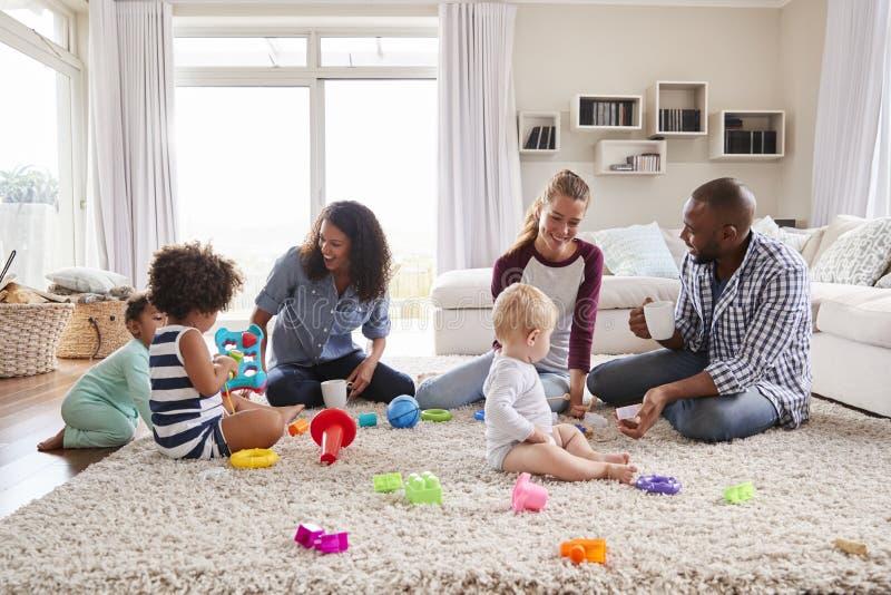 Tre vänner som spelar med små barn på vardagsrumgolv arkivbild