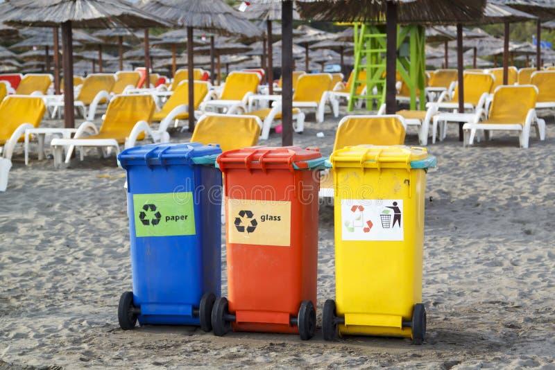 Tre variopinti riciclano i recipienti sulla spiaggia fotografie stock