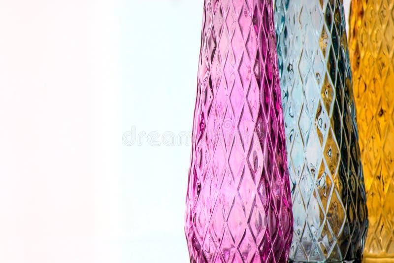 Tre vasi di vetro colorato con un modello fotografia stock