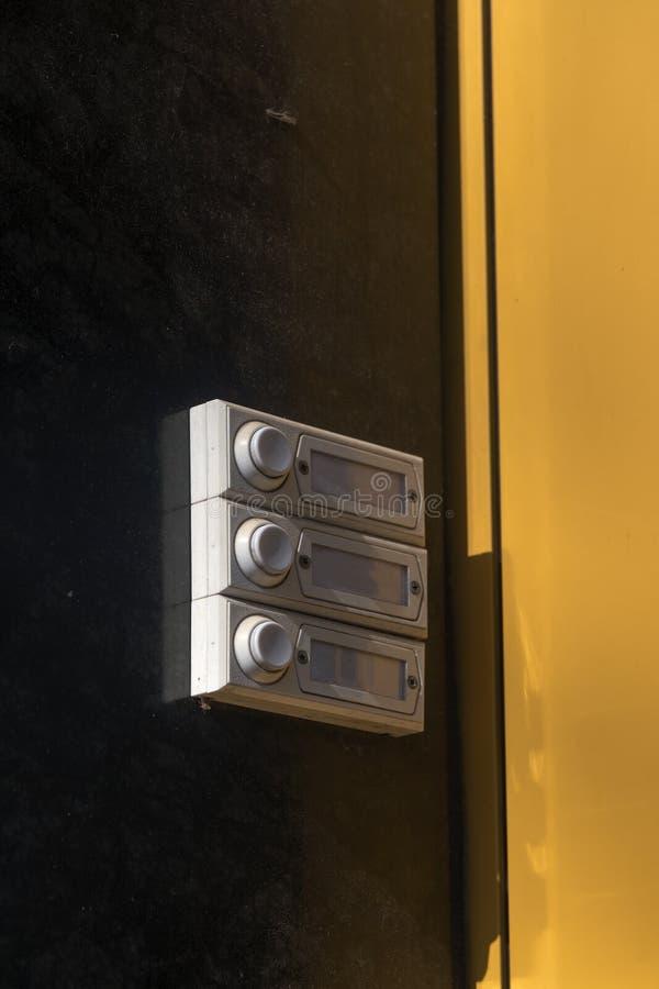 Tre vecchi campanelli per porte su una parete gialla marrone di un buil dell'appartamento fotografie stock