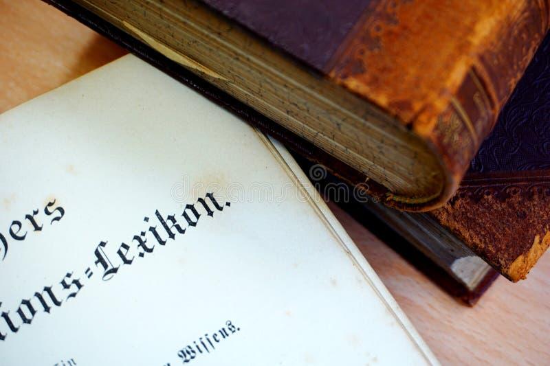 Tre vecchi libri sulla tavola ed aprono la pagina anteriore di vecchio lessico immagini stock libere da diritti