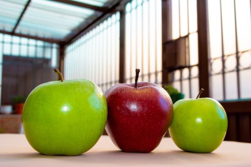 Tre verdi e mele rosse con le luci variopinte immagine stock libera da diritti