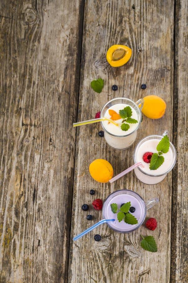 Tre vetri con i frullati o il yogurt con le bacche fresche sulla a fotografie stock
