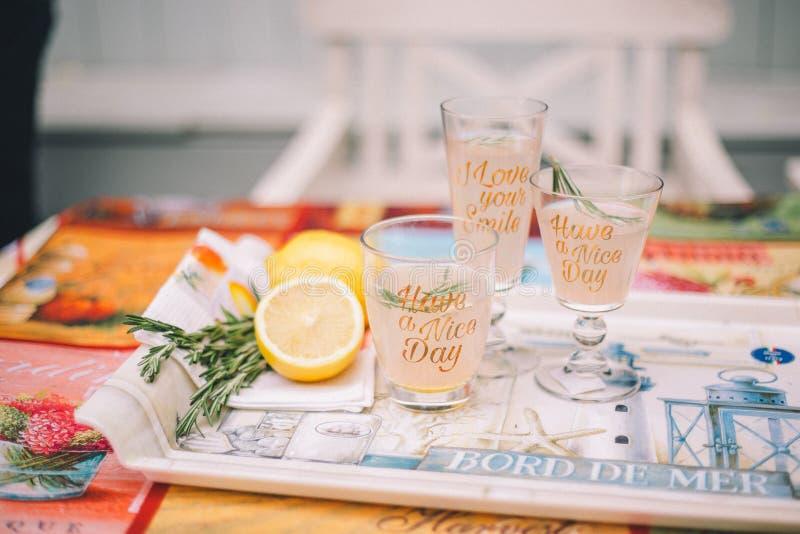 Tre vetri con le bevande dell'agrume su un vassoio Dopo sar? il limone ed il rosmarino affettati fotografie stock libere da diritti
