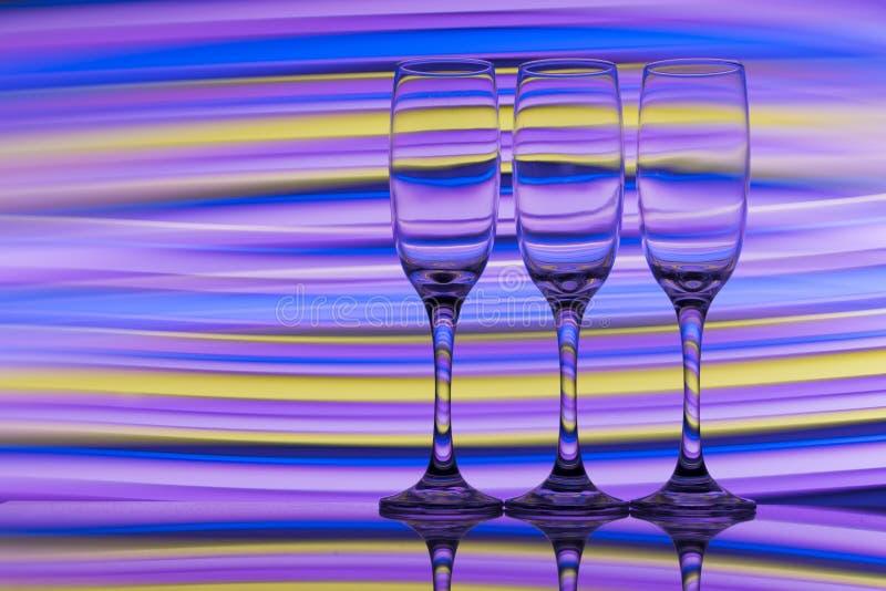 Tre vetri del champagne in una fila con un arcobaleno di pittura leggera variopinta dietro loro immagine stock