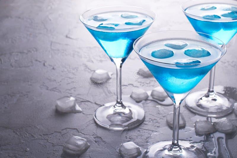 Tre vetri del cocktail freddo blu di martini con ghiaccio e di chiare gocce di rugiada su vetro su un fondo concreto grigio fotografia stock