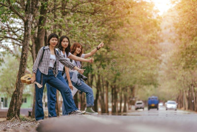 Tre viaggiatori con zaino e sacco a pelo interrazziali felici della ragazza giovani, dividenti un giro sulla vacanza fotografia stock libera da diritti