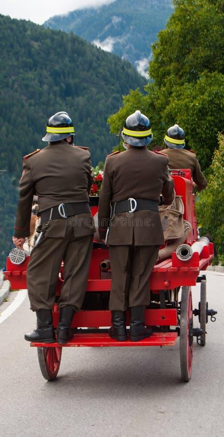 Tre vigili del fuoco sul trasporto rosso con i cavalli del passato fotografia stock libera da diritti