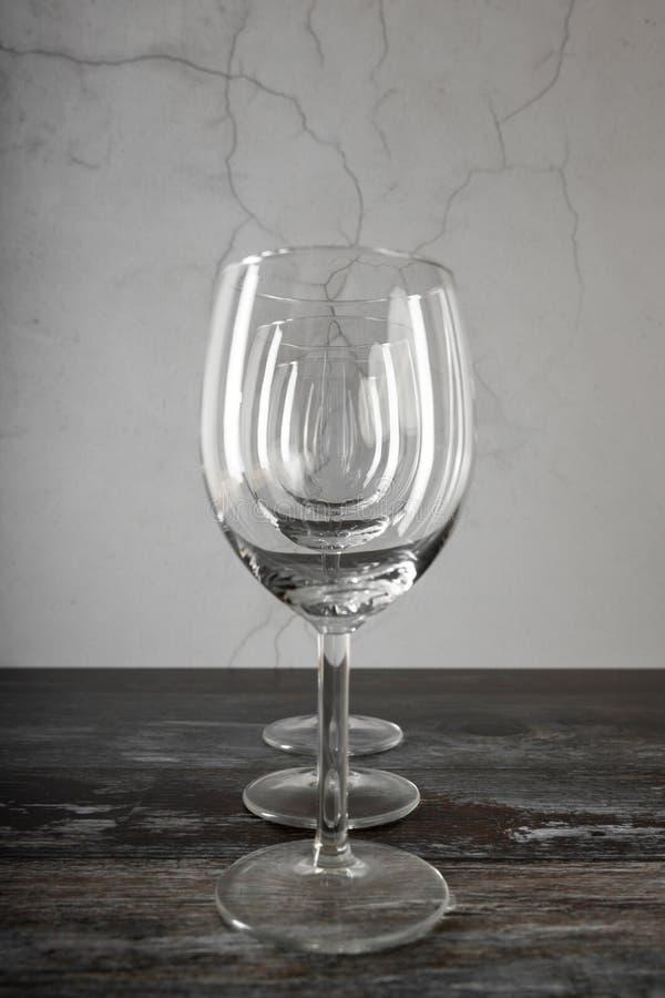 Tre vinexponeringsglas på trätabellen arkivfoto