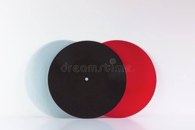 Tre vinyler, blått, svart och rött, på vit bakgrund, med tomt utrymme royaltyfria bilder