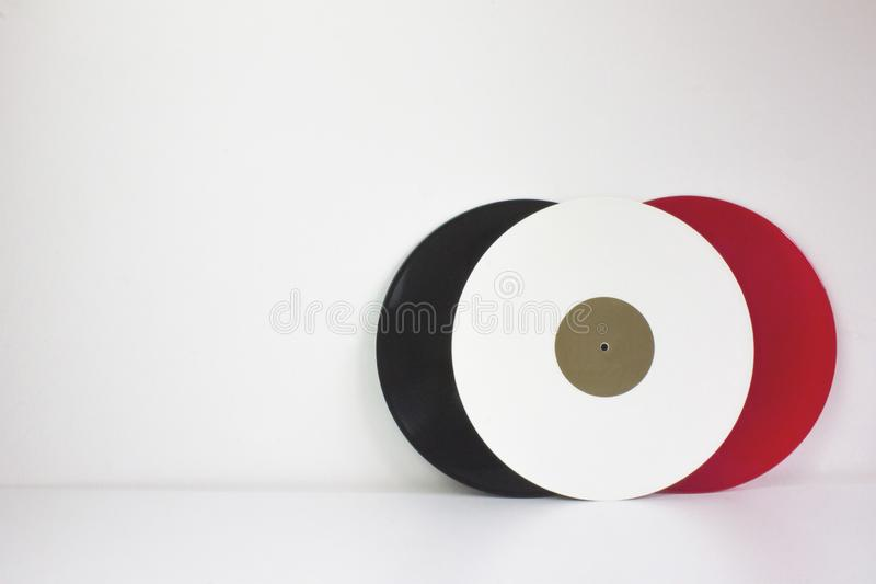 Tre vinyler, svart, rött och vitt, på vit bakgrund, med vitt utrymme arkivfoton