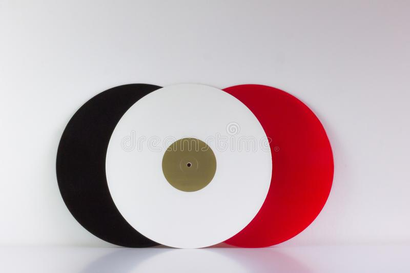 Tre vinyler, svart, rött och vitt, på vit bakgrund, med vitt utrymme royaltyfria bilder