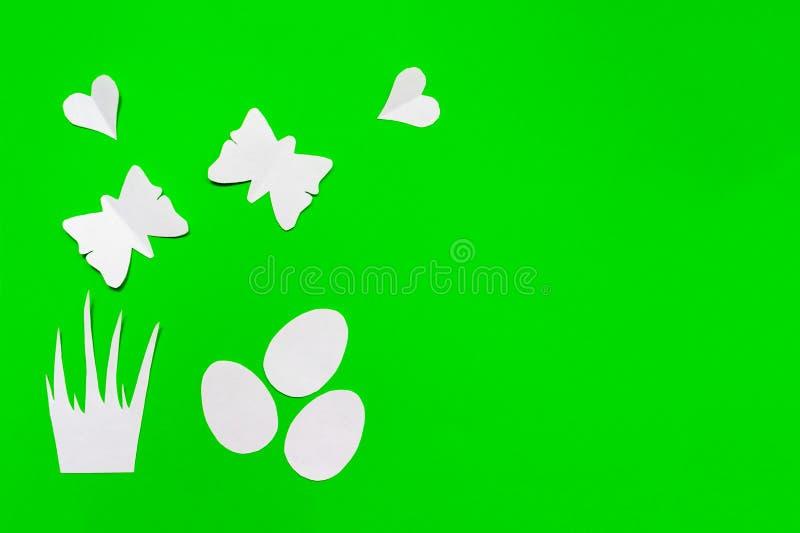 Tre vita easter ägg, gräs, hjärtor och fjärilssnitt av papper på grönt bakgrunds-, easter och vårbegrepp arkivfoto