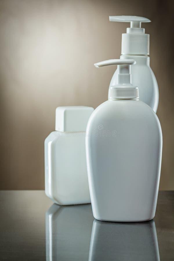 Tre vita sprutor och en flaska med lotion och kräm på vintag bakgrund royaltyfria foton