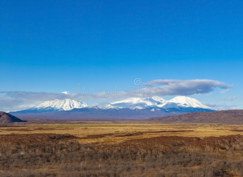Tre volcanoes i den Kamchatka halv?n arkivfoton