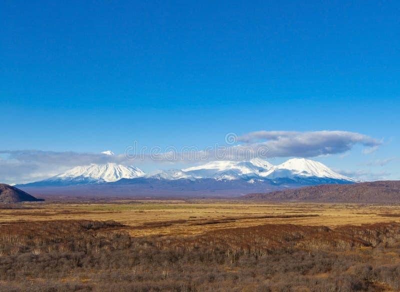 Tre volcanoes i den Kamchatka halv?n royaltyfri bild